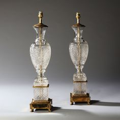 Pair of clear cut glass table lamps of baluster form, raised on square glass plinths with further cutting and lacquered brass bases with lions paw feet.   Retailed by Harrods