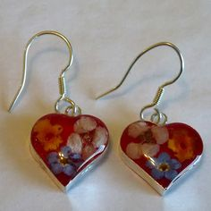 Real Flower Jewelry. Red Heart Earrings. The flowers are real flowers grown without fertilizers or pesticides. Earrings are made through cottage industry in Taxco Mexico.  Margarito Santos and his brother started the business and with a small team of workers they grow the flowers and make the jewelry in their homes, encasing and preserving the flowers. Fair Trade!