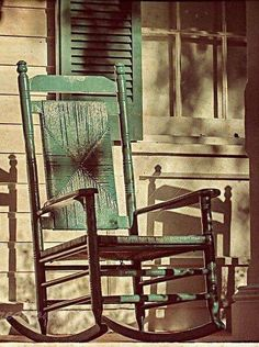 Faded Green Rocking Chair On A Porch