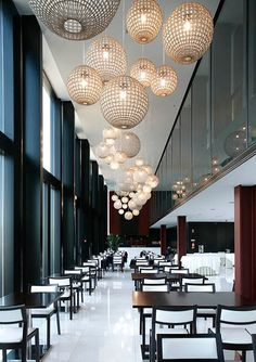 Clusters of large pendant lamps create a cool ceiling light feature and draw your eye through the restaurant #restaurantlighting: