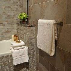 Large #bathroom tiles and folded #towels. Love those #warm earth tones
