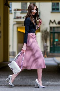 Street style look com saia plissada rosa, salto e bolsa metalizados, blusa preta manga longa e óculos de sol espelhado.