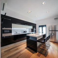 modern black kitchen high gloss black cabinetry white countertop
