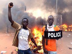 Manifestantes posam em frente ao Parlamento de Ouagadougou, em Burkina Faso. Centenas de pessoas invadiram o parlamento e colocaram fogo em protesto contra os planos de mudar a constituição para o presidente Blaise Compaoré ampliar seu mandato de 27 anos (Foto: Issouf Sanogo/AFP)