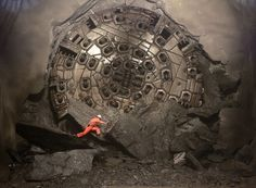 A miner climbs on excavated rocks after a giant Sissi drill machine broke through the last section of rock at the construction site of the NEAT Gotthard Base Tunnel in Switzerland on March 23, 2011. Crossing the Alps, the world's longest train tunnel consists of two, parallel, single-track tunnels, each a length of 35 miles. The project should become operational at the end of 2016