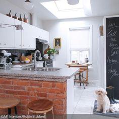 Dieser Küchentresen mit Backsteinen verleiht der Küche einen coolen Retro-Charme. Verschiedene Barhocker und eine zur Tafel umfunktionierte Zimmerwand  …