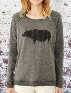 This womens locker room pullover features an original illustration of a grizzly bear silhouette above pine covered mountain ridges. The art is