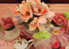 I am the owner and operator of Tea in Tiaras and this was my own Princess Tea Party design.  I found these flowers at a discount party supply store and set them in china tea cups and saucers with Spanish moss.  The other piece is a teapot with floral foam and Spanish Moss.  Detailed with clip on butterflies, bircages with feather birds, table pearls and jewels and many more little bits of whimsy!
