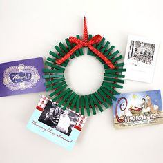Decorate your #wreath with the faces of the people you love! Clip painted clothespins around a bent wire hanger, then insert the day's haul of holiday cards for all to see.