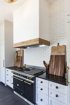 A white kitchen hood accented with a rustic wood trim is mounted on an exposed…