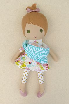 Custom listing for Saioa:  This is a handmade cloth doll measuring 20 inches. She is wearing a sweet, pink and green floral dress with a matching, removable skirt, gold polka dotted leggings, and pink shoes. She carries a pink polka dotted, flannel baby in a blue and white patterned sling. Her light brown hair is worn in a high, wild ponytail and accented with a matching, pink fabric bow. She is made from 100% cotton fabrics, wool blend felt, and polyester fiberfill. Her seams are triple…
