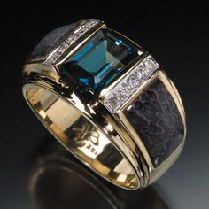 RANDY POLK DESIGNS: MEN'S RINGS. 9x7mm London blue topaz center stone with inlay and 10 pave diamonds