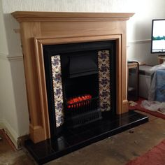 Lovely gallery cast with black tiled hearth,oak surround and electric fire