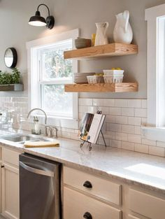 gooseneck lamp, white kitchen cabinets, white subway tile and walls painted Sherwin Williams Mindful Gray, open shelving