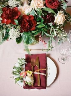 burgundy place setting with gold flatware and a lush centerpiece