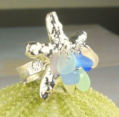 This beautiful all Sterling Silver, Starfish ring is highlighted by a perfect, ocean-tumbled pastel sea glass gems in a rare yellow, pink, sea foam, cornflower, cobalt, lime green and turquoise. It is an adjustable size ring as seen by the pictures and will fit all sizes. The sterling on the ring is magnificent and has pretty shell and fish etchings on the band. The ring is a sturdy piece - thick and SOLID .925 Sterling Silver and in a gorgeous, textured starfish design - a perfect ...
