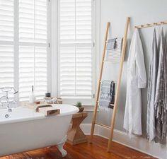 Baño de estilo clásico con escalera utilizada como toallero, suelo de madera y bañera de pie