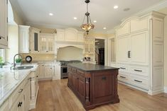 Large white kitchen with custom ornate cabinetry and dark brown ornate island.