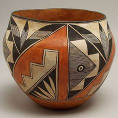 VINTAGE ACOMA PUEBLO INDIAN POTTERY BOWL : With dimpled base, the exterior with four rectangular panels each bisected diagonally and enclosing stairstep and feather motifs. Beigeware with orange, white, brown and black paints. Circa mid-20th century. Height: 7 1/2 inches; diameter: 9 inches