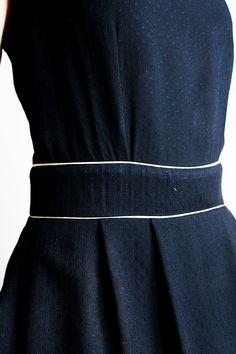 Robe en viscose noir à petits motifs brodés, plis devant et dos, biais or à la ceinture