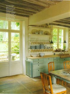 A kitchen with no upper cabinets, plenty of light, and a table (instead of an island).