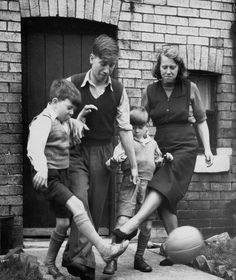 Elizabeth Charlton playing a game of football with her three sons Gordon aged 10, Bobby 15 and Tommy 7 outside their home. Bobby went on to play for Manchester United and England winning the World Cup in 1966 and European Cup in 1968. 10th June 1953.