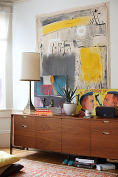 yellow and grey painting by Indian artist Suhas Shilker sits atop a mid-century console in this San Francisco two-room apartment of a world traveler.