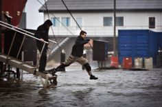 HOP AND SKIP: A man jumped into floodwaters in Hvide Sande, Denmark, after a storm flooded the harbor Thursday. The storm disrupted travel a...