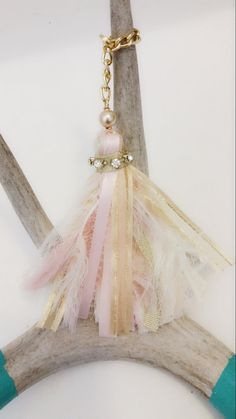 This tassel is gorgeous. The soft pinks, ivories and gold hues look dainty with a shabby chic look. A gold pearl bead and some bling to