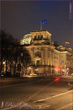 Building of the German Parliament - Deutscher Bundestag with german flag by night - Reichstagsgebäude - view from Brandenburger Gate, Platz des 18. März - Berlin Germany/Deutschland