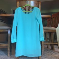 Mint Blue Shift Dress with Criss Cross Low Back This dress is super cute! I wore it once to a graduation with tan wedges. It has a low cut Criss cross back and the sleeves have little buttons on them. The brand is The Clothing Company and I bought it on Lulu's. Lulu's Dresses Mini