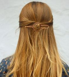 Accessorize your tresses with this minimalist metal hair barrette. Each one is hand hammered in copper, brass or silver, the thick wire sturdy enough to hold up even thick and heavy hair. Simply place the organically shaped oval over a twist or small bun, and use the two-pronged fork to hold your hairdo in place. The fork can also be used alone to stick into a bun or French twist.