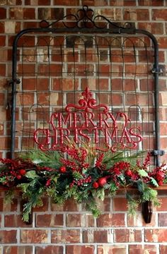 Gorgeous metal Merry Christmas on a heavy iron base tucked into greenery on a mantle. From the blog Back Porch Musings.: