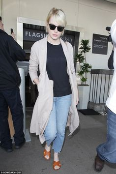First class fashion:Emma Stone was proving 'less is more' when she jetted comfortably into LAX, keeping it casual in baggy jeans and a black top