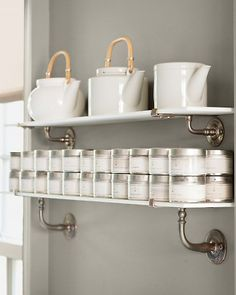 """Need more space? Sneak in more shelves - """"In a kitchen, unused wall space is wasted space,"""" Martha says. Thin shelves -- these are antique milk glass -- add storage without feeling heavy or imposing, even in a tight spot. These hold teapots and spices (metal tins keep light out so spices last longer)."""