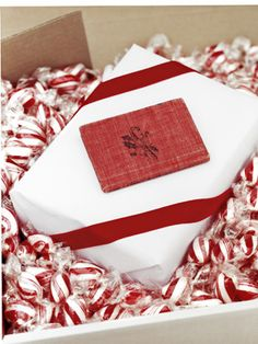 Creative Christmas Gift Wrapping Ideas-Cushion your presents with candy! Replace boring Styrofoam with swirls of minty goodness, then wrap your gifts in the red-and-white color combination for an eye-catching display.  #lulusholiday
