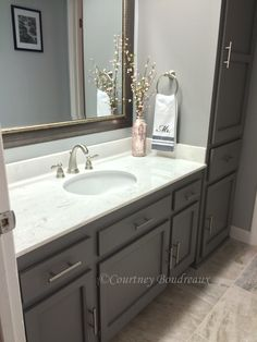 Grey and White bathroom. #Behr Paint using color #Anonymous for the cabinets and Light French Grey on walls. Cultured marble countertops with an oval undermount sink and Delta Brushed Nickel fixtures. Mirror is from Kirkland's and floors are Broadmoor tile from the Home depot.