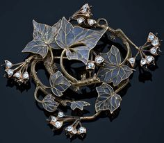 RENÉ LALIQUE. 1900 Brooch w/yellow-gold  branches, leaves and buds. Spiral branches and plique-à-jour leaves and buds of black enamel and small diamonds.