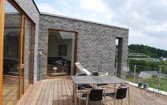 Terrasse i hårdtræsplanker og vinduer i teaktræ.
