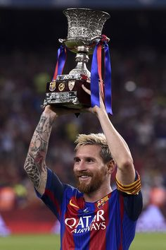 Barcelona's Argentinian forward Lionel Messi holds the Spanish Supercup trophy…