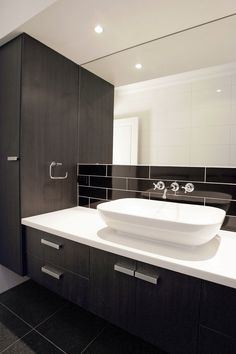 The deep tones of the cupboards contrast beautifully with the white basin. Not to mention those gorgeous black subway tiles. #bathroom #black #statement #tiles