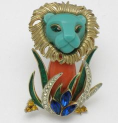 Iconic and very hard to find vintage Hattie Carnegie 'Lion in the Grass' brooch or pin. This pin is not signed but you can see where the oval cartouche signature was - see photos. He has a turquoise blue and orange resin or thermoplastic face and body with sapphire blue rhinestone eyes. A textured gold plated mane is around his head. He is sitting in the grass which is a combination of green enamel and crystal clear pave or diamante stones. Three sapphire marquise stones and amber…