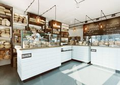 Wire-encased lights are suspended above oak-topped counters at this bakery in Poland by designer Maciej Kurkowski