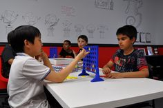 Foreground: Ian playing Connect Four with Radhika's brother. Background: Jaylen playing Connect Four and Shervin enjoying some pizza.