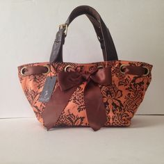 """NWT Imoshion Brown and Orange Handbag NWT. Adorable floral pattern on this small tote bag. Canvas with a ribbon at the top, like a bucket bag. Has a zipper closure. Insert at the bottom that is removable. Brass hardware with buckle detail on the straps. 5 hooks for adjusting. Feet on the bottom. 2 pockets inside, 1 of them zips. Absolutely Adorable!! Strap drop is 8"""" in middle hook. Imoshion Bags Totes"""