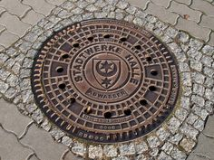 This manhole cover in Halle (Saale) displays the coat of arms of the city. The city arms of Halle consist of a moon between two stars of different size. Saxony Anhalt, Rhineland Palatinate, Lower Saxony, North Rhine Westphalia, Coat Of Arms, Halle, Cover Art, Dna, Metal Working
