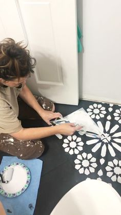 Painting the stencil design on a tile floor