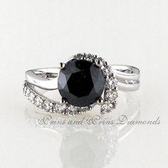 Centre diamond is a 5.15ct round cut black diamond with 0.15t round brilliant cut white diamonds set in a twisty half halo 18k white gold design