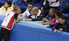 Evgeny Plyushchenko of Russia, left, speaks with his coach Alexei Mishin, centre right, during a men's figure skating training session at th...