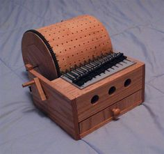 DIY programmable music box- uses a wooden drum with holes for pegs, pegs can be placed in any pattern to create any tune